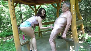 Outdoors video of a naughty teen stroking a dick of an older man
