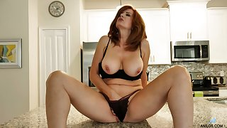 Red haired MILF undresses and plays with her appetizing big boobies